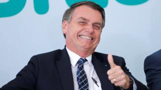 Brazil's President Jair Bolsonaro gives a thumbs up during a ceremony in Brasilia