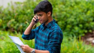 Student on phone looking at results letter