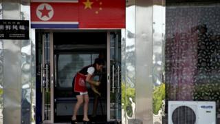 Norte-coreana limpa chão em um restaurante em Dandong, na China, onde milhares de trabalhadores norte-coreanos vivem