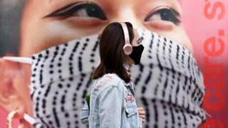 A pedestrian wearing a face mask walks past a poster of a person wearing a face covering on a high street in west London - 11 October 2020