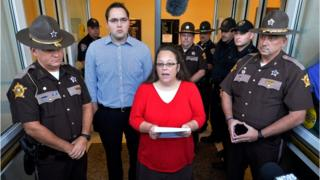 """Surrounded by Rowan County Sheriff""""s deputies, Rowan County Clerk Kim Davis, centre, with her son Nathan Davis standing by her side, makes a statement to the media at the front door of the Rowan County Judicial Center in Morehead, Kentucky, on Monday"""