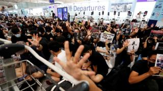 Anti-government protesters react after the announcement that all airport operations are suspended
