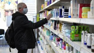 A man with a mask on in a pharmacy