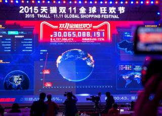 People take photos of a large screen showing total gross merchandise volume, a measure of sales, exceeding 10 billion yuan at 00:12 am and 28 seconds during the 2015 Tmall 11:11 Global Shopping Festival gala in Beijing on 11 November 2015