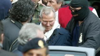Mafia boss Bernardo Provenzano with hooded police officers after his capture in Palermo, Sicily, southern Italy, 11 April 2006