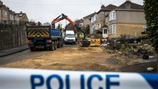Workers remove debris at the crash site on Lansdown Lane in Bath