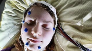 فتاة أثناء نومها وخضوعها لدراسة تتعلق بأهمية النوم