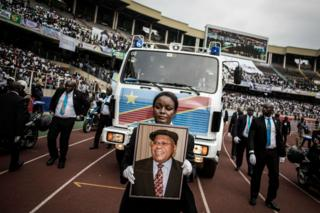 A woman holds the portrait of late former DR Congo Prime Minister and opposition leader Etienne Tshisekedi as his remains arrive at the mourning ceremony.