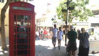 Red telephone kiosk on a street in Gibraltar