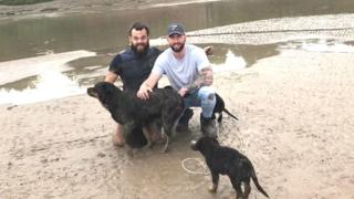 Jonathan Powell and Sean Lomas with Bella the dog, who the pair saved from estuary mud in Gloucestershire