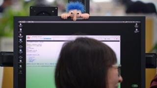 Long nosed troll hangs over a Chinese woman's computer monitor