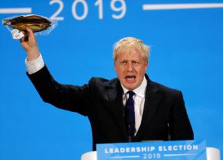 Boris Johnson waves a plastic-wrapped smoked kipper in the air at the final Conservative leadership hustings in London