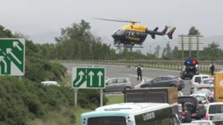 A helicopter takes off from the scene of the crash