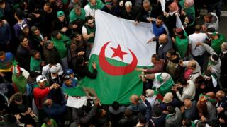 Algerians protesting with a flag