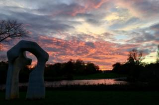 Sunset over a river with by a sculpture