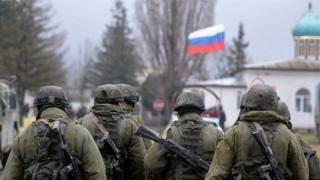 Озброєні військові в Криму на тлі російського прапора