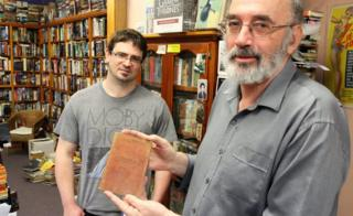 Co-owners of the Cracked and Spineless bookshop, Richard Sprent (left) and Mike Gray, with the journal, standing inside the shop