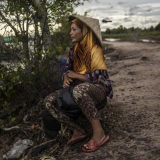 A woman waits for the fishermen to return