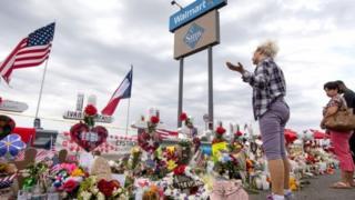 Três pessoas em frente a flores e outras demonstrações de homeangem em área externa do local onde ocorreu ataque em El Paso