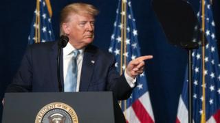 Em parlatório, Trump olha e aponta para o lado