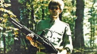 Technology Handout picture shows a man holding a weapon in a forest