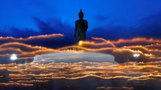 Buddhists carry candles while circling a large Buddha statue during Asanha Bucha Day