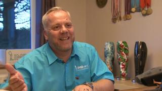 Mark Williams at home with three prosethetic legs and some medals in the background
