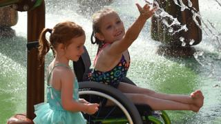 Two girls enjoying a fountain