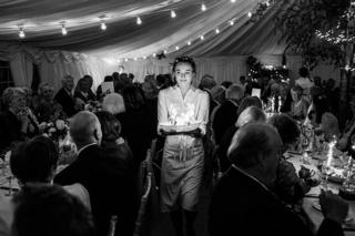 A waitress carries food through a wedding reception