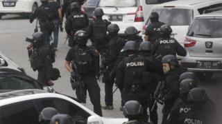 事件現場に入る重装備の警官隊(14日)