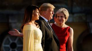 Prime Minister Theresa May directs US First Lady Melania Trump and US President Donald Trump after a ceremonial welcome for a black-tie dinner with business leaders at Blenheim Palace