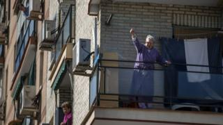 A woman reacts from a balcony to a protest during the International Women's Day on March 08
