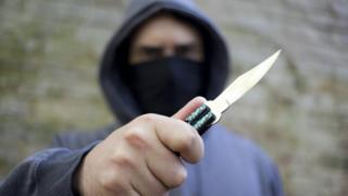 A hooded youth brandishes a knife