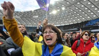 Женщина кричит в толпе