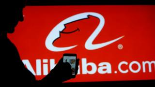 A woman searches online on a mobile phone from Alibaba.com in Moscow, Russia, September 11, 2018.