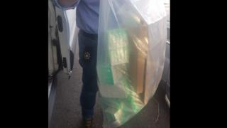 PSNI officer holding an evidence bag of seized drugs