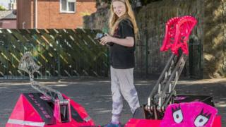 Eleven-year-old April Prince with two robots she engineered
