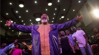 Worshippers pray during Sunday service at the House of Praise church in London