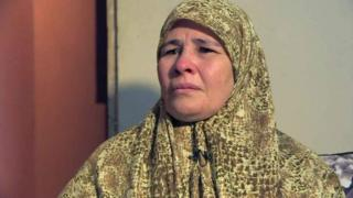 A woman wearing a headscarf looks slight off camera, clearly in emotional distress, during a BBC interview