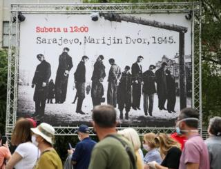 People march past a poster that shows Nazi victims during World War Two