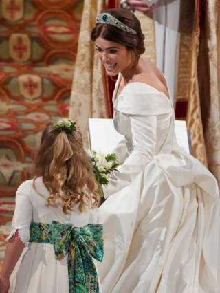 Princess Eugenie of York passes her bouquet to bridesmaid