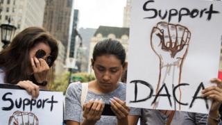 Jóvenes lloran y miran el anuncio del fin de DACA.