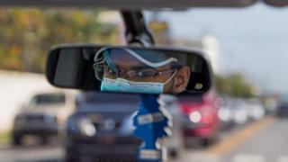 A Uber driver wears a face mask as seen in his rearview mirror