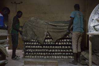 Workers at Buru Niouman Bakery in Bamako, Mali unveil racks of dough that are ready to be baked. 5 February 2019.