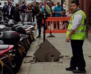 Man beside exploded electrical manhole