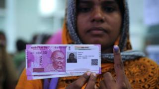 An Indian woman poses with new 2000 rupee notes, her Aadhaar ID card and a finger inked with indelible ink after exchanging withdrawn 500 and 1000 rupee banknotes at a bank in Chennai on November 17, 2016