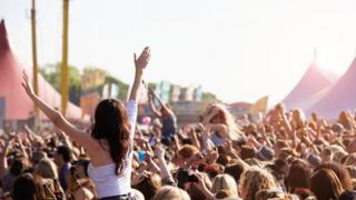 Young woman in a crowd with her hands in the air at a music festival.