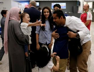 A family hug each other at Washington Dulles Airport on 26 June, 2017, after the U.S. Supreme Court granted parts of the Trump administration's emergency request to put its travel ban into effect