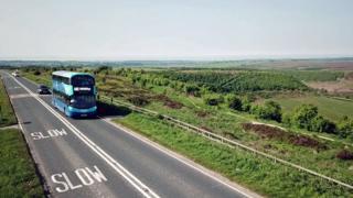 Double-decker bus going through open countryside