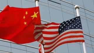 A US and a Chinese flag wave outside a commercial building in Beijing (9 July 2007)